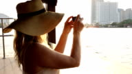 Woman takes pic of city, Chao Phraya River, from river boat video