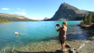 Woman takes picture of mountain lake using digital tablet video