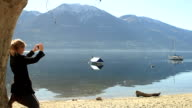 Woman takes picture of mountain lake with mobile phone video