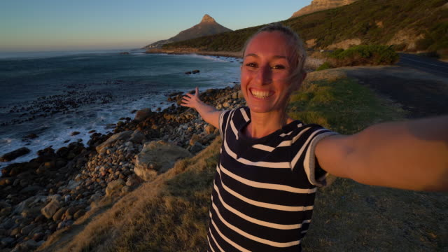 Woman takes self portrait photo by the coast in Cape Town video