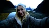 Woman takes selfie portrait at Milford sound video