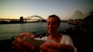 Woman takes selfie portrait in Sydney harbor using mobile phone video