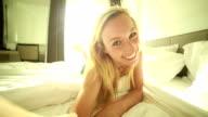 Woman taking a selfie in hotel bedroom video