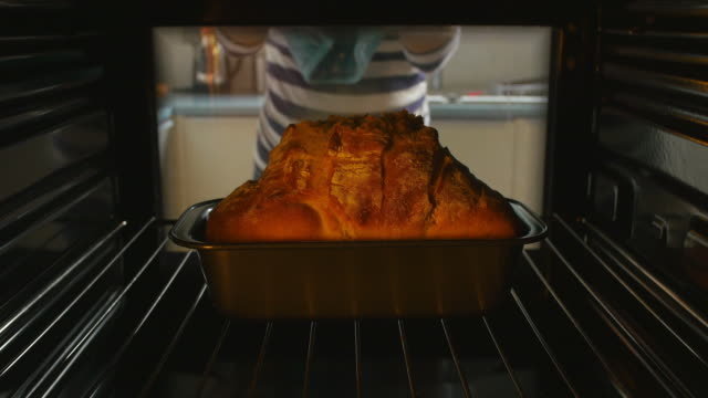 Woman Taking Baked Loaf Of Bread Out Of The Oven video