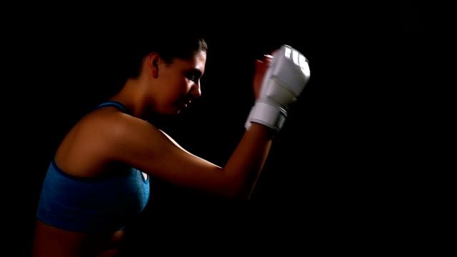 Woman taking breath tired exhausted disappointed after boxing kicking, black background, slow motion video