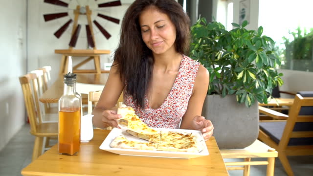 Woman taking cheese pizza cut video