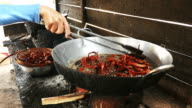 Woman taking fried snakes out of the wok video