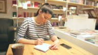 Woman taking notes in the bookstore. video