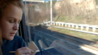 Woman taking notes or drawing in train video