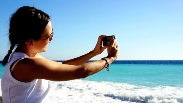 Woman taking photo with cellphone on the beach video