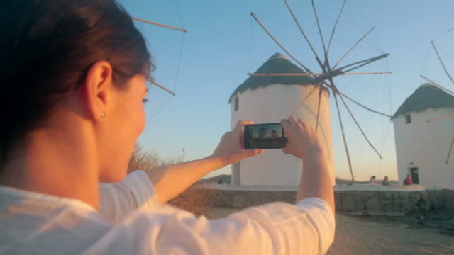 Woman taking pictures at Windmills in Mykonos, Greece. video