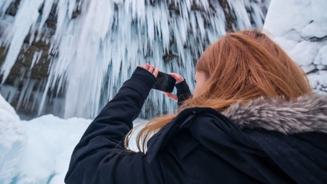 Woman taking pictures of beautiful frozen waterfall video