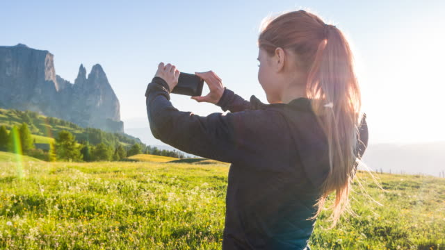 Woman taking pictures of landscape in the Alps in summer video