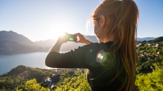 Woman taking pictures of panoramic view of lake and lakeside village video