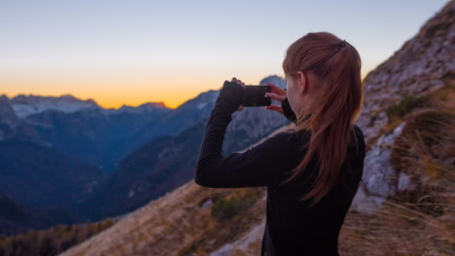Woman taking pictures of the beautiful view with her smartphone video