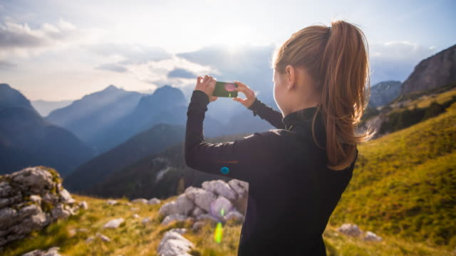 Woman taking pictures of the mountainside with smartphone video