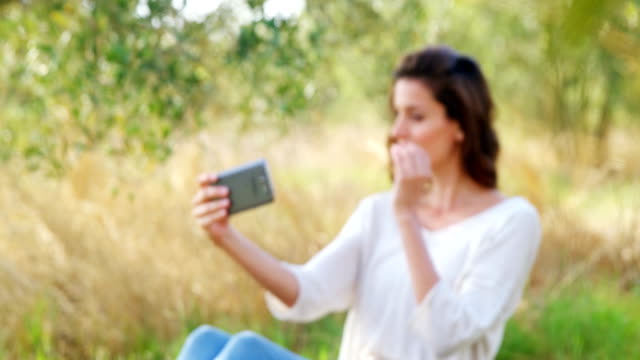 Woman taking selfie from mobile phone in olive farm 4k video