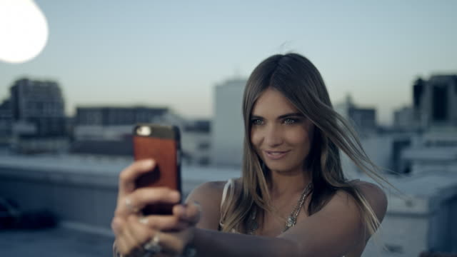 Woman taking selfie on rooftop video