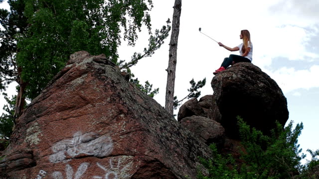 Woman taking self-portrait with phone in mountains video