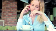 Woman talking on cellphone and drinking cafe latte in cafe video