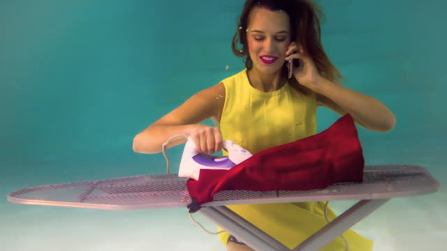 Woman Talking On Mobile and Ironing Under Water video