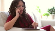 Woman talking on the phone and using tablet pc video