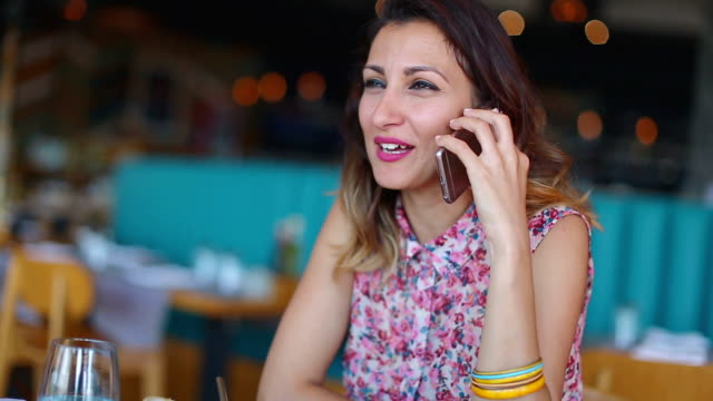 Woman talking on the phone in restaurant video