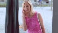 Woman talking on the phone while standing at the display window video