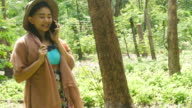 woman talking smart-phone and walking in forest video