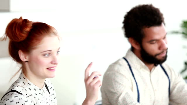 Woman talking with colleagues at office meeting, male colleague in background video