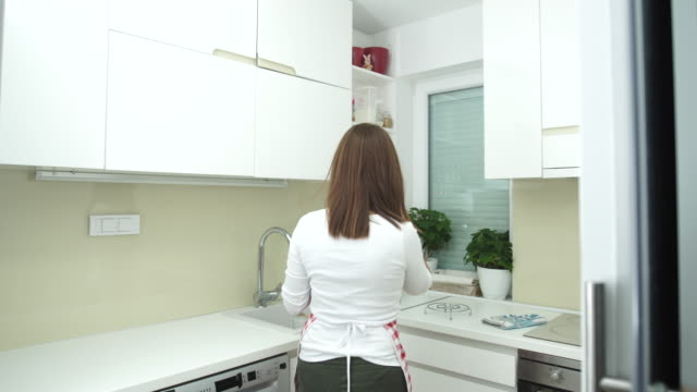 Woman talks on mobile in kitchen 4K video