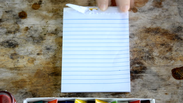 Woman tearing blank notepad on table may use for presentation video