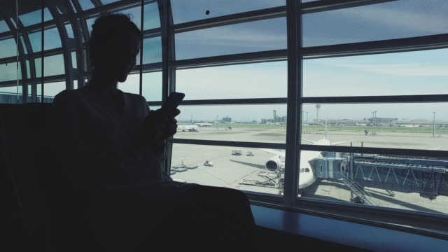 Woman texting at the airport lounge video