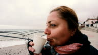 woman, that looks funny, drinking coffee on the cold beach video