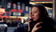 Young woman tired of waiting talks on phone sitting at bus stop video