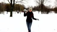 Woman toss snowball and hit on camera, snow splash across screen video