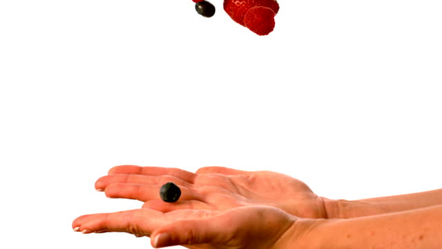 Woman tossing berries on white background video
