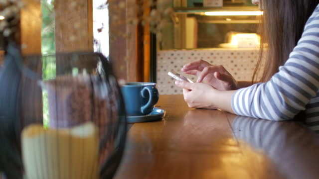 Woman touching smartphone on the table with coffee at coffee cafe video