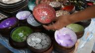 Woman tourist choosing a coconut shell at souvenir shop in Thailand. video