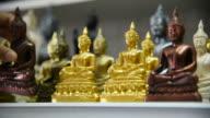 Woman tourist choosing Buddha at souvenir shop in Thailand. video