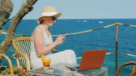 Woman tourist relaxing in a cafe overlooking the sea, enjoys a smartphone, standing next to a laptop video