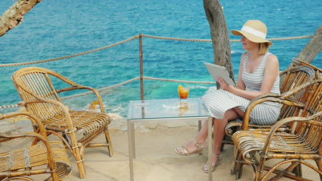 Woman tourist speaks with the tablet, always-on connection. Videochat of scenic spot overlooking the sea video