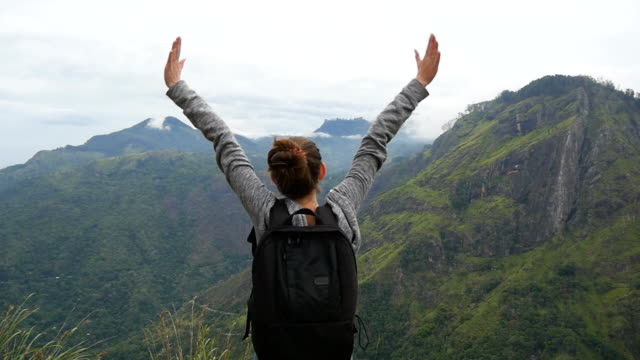 Woman tourist standing on edge of beautiful canyon, victoriously outstretching arms up and enjoying freedom. Young female hiker with backpack reaching up top of mountain and raised hands. Slow motion video