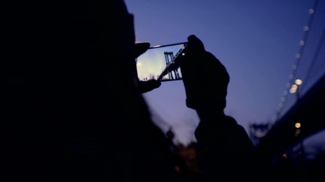 Woman tourist using smartphone take a photo of sunset video