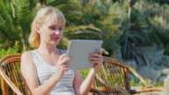 Woman tourist with the tablet says. He sits in a wicker chair on the background of palm trees. Always connected on a tropical resort video