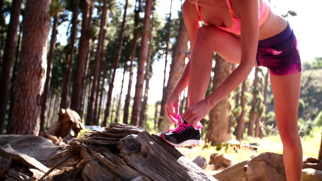 Woman trail runner fixing her shoelaces on her running shoes video