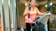 Woman trains on stepper machine in gym. Concept of health and fitness. video