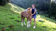 Woman traveler in the mountains playing with foal video