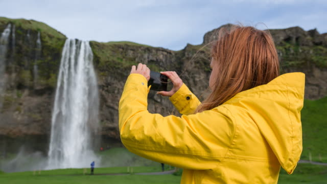 Woman traveling Iceland, taking pictures of natural landmarks video