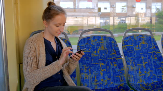 Woman travelling by tram and using smartphone video